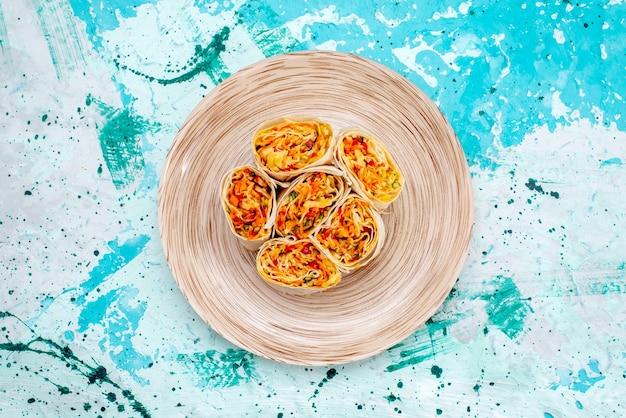 Vista superior de la masa de rollos de verduras en rodajas con relleno en la mesa de color azul brillante, comida, foto, rollo de color vegetal