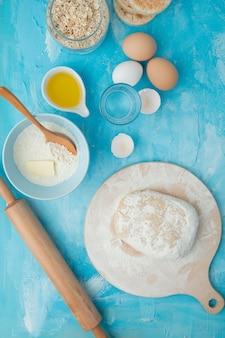 Vista superior de la masa sobre una tabla rodante y harina de mantequilla huevos agua con rodillo sobre fondo azul.