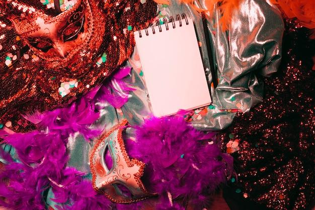 Vista superior de la máscara de carnaval; boa de plumas blandas y bloc de notas en espiral.