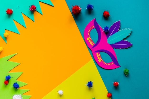 Vista superior de la máscara de carnaval y coloridos pompones