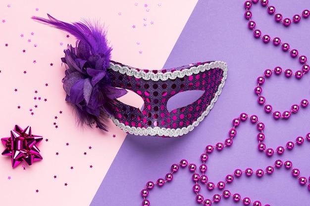 Vista superior de la máscara de carnaval con plumas y purpurina.