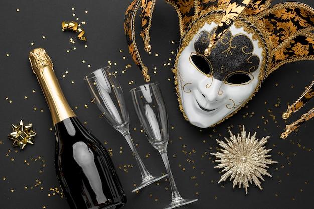 Vista superior de la máscara de carnaval con purpurina y botella de champán.