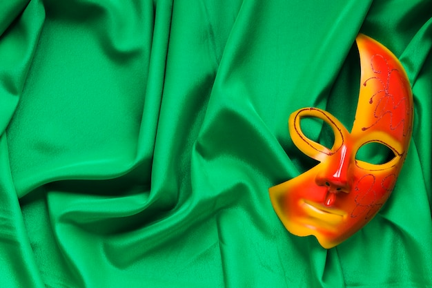 Vista superior de máscara para carnaval sobre tela verde