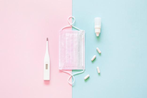 Vista superior de la máscara médica, píldoras y termómetro sobre fondo rosa y verde.