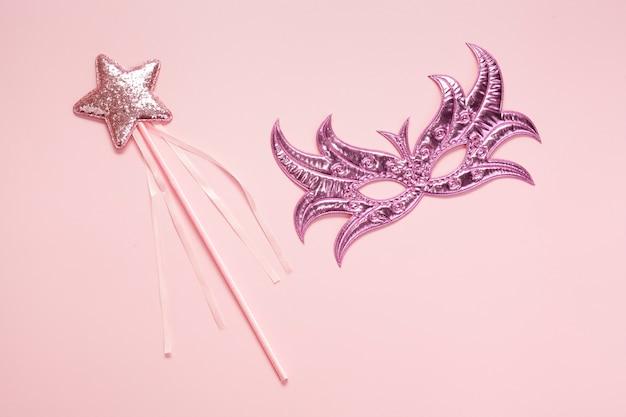 Vista superior máscara rosa y estrella en palo