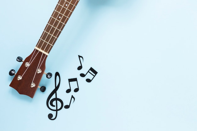 Vista superior del mástil de guitarra con notas musicales.