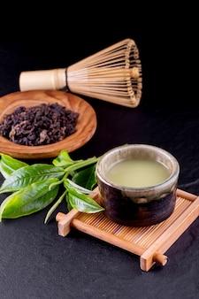 Vista superior del matcha del té verde en un cuenco en superficie de madera