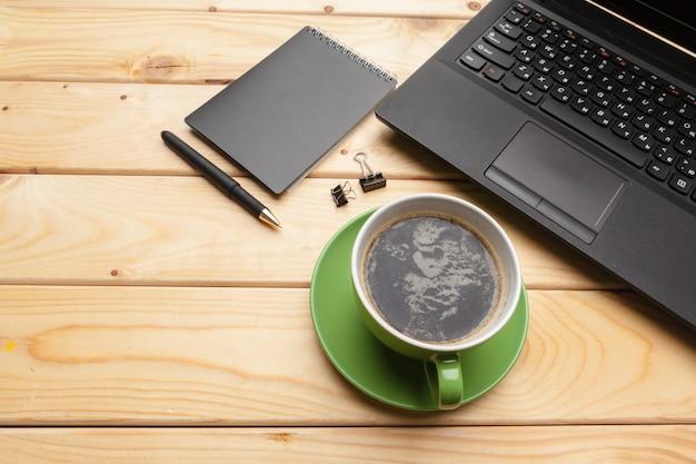 Vista superior de material de oficina con laptop y café