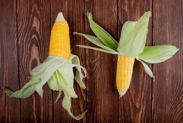 Vista superior de mazorcas de maíz con cáscara en madera
