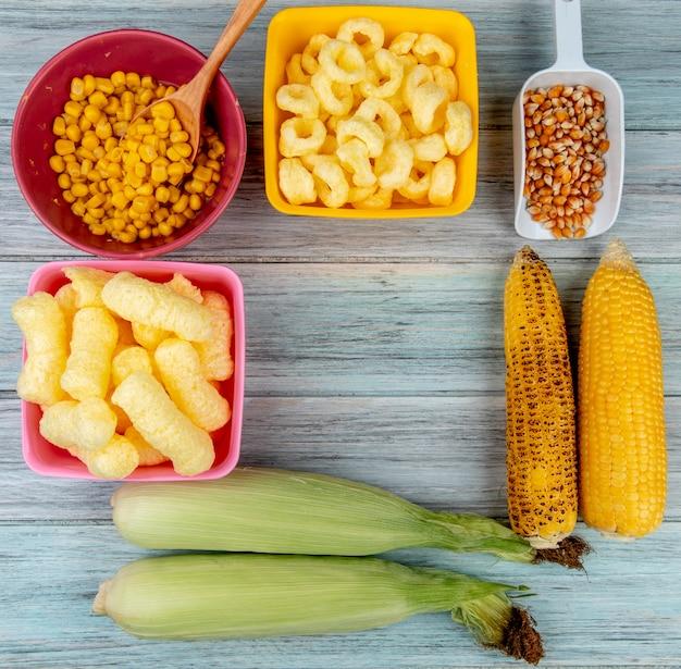 Vista superior de mazorcas de maíz con cereales pop de maíz y semillas de maíz en superficie de madera
