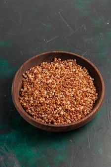 Vista superior de media comida sabrosa de trigo sarraceno cocido dentro de la placa marrón sobre la superficie verde oscuro