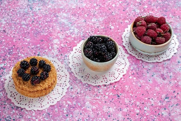 Vista superior de media tarta de moras con frambuesas y moras frescas sobre el fondo rosa claro.