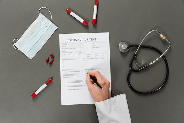 Vista superior del médico escribiendo en una prueba de coronavirus