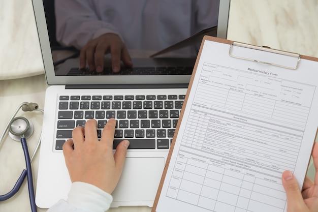 Vista superior del médico usando un portátil y un portapapeles