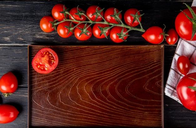 Vista superior de medio tomate cortado en bandeja y enteros sobre superficie de madera