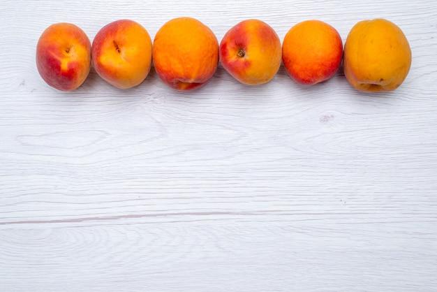 Una vista superior de melocotones frescos y suaves sobre el fondo blanco color de la fruta fresca