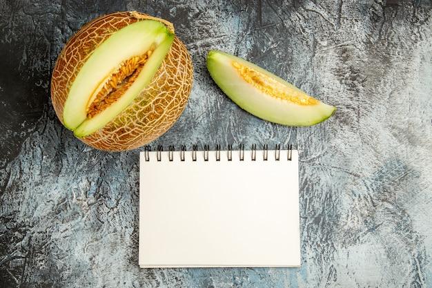 Vista superior de melón fresco en rodajas en la mesa de luz oscura dulce fruta verano suave