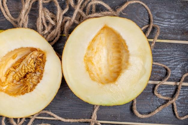 Vista superior de melón en rodajas mitad fruta dulce cortada en el fondo rústico marrón