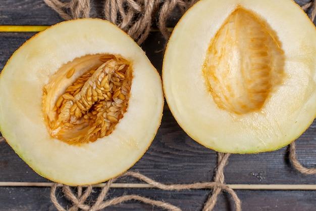 Vista superior de melón en rodajas mitad fruta dulce cortada sobre el fondo marrón
