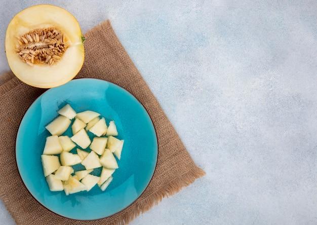 Vista superior del melón en rodajas en una placa azul sobre tela de saco en la superficie blanca