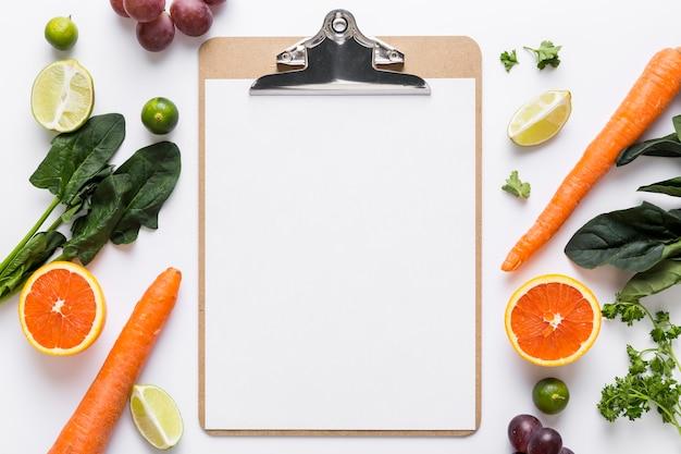 Vista superior del menú en blanco con espinacas y zanahorias