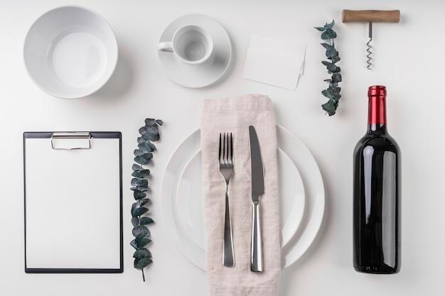 Vista superior del menú vacío con platos y botella de vino.