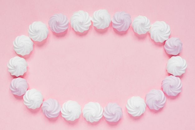 Vista superior de merengues retorcidos blancos y rosados sobre fondo rosa