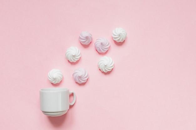 Vista superior de merengues retorcidos blancos y rosados y taza de café sobre fondo rosa con espacio de copia