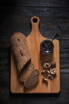 La vista superior de mermelada afrutada en mesa de madera negra