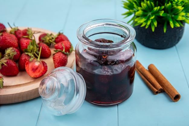 Vista superior de mermelada de fresa en un frasco de vidrio con ramas de canela con fresas frescas en una tabla de cocina de madera sobre un fondo azul.