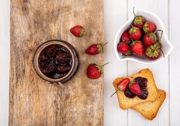 Vista superior de mermelada de fresa en un frasco de vidrio sobre una tabla de cocina de madera con fresas frescas en un recipiente blanco con rebanadas de pan tostado sobre un fondo blanco de madera