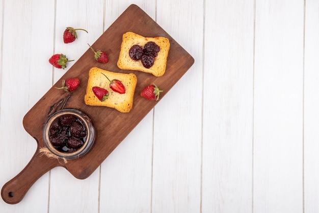 Vista superior de mermelada de fresa en una tabla de cocina de madera con pan tostado sobre un fondo de madera blanca con espacio de copia