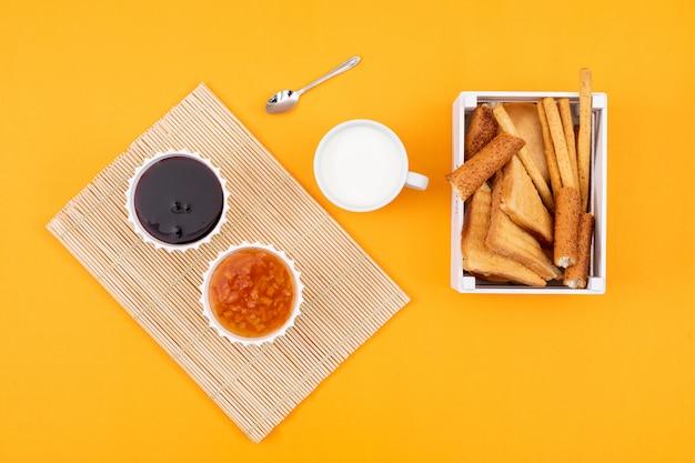 Vista superior de mermelada con leche y tostadas en superficie amarilla horizontal
