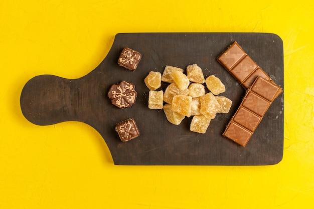 Vista superior de mermelada en rodajas dulce y confituras en rodajas de azúcar con barras de chocolate sobre superficie amarilla