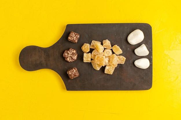 Vista superior de mermelada en rodajas dulce y confituras en rodajas de azúcar con chocolate sobre superficie amarilla