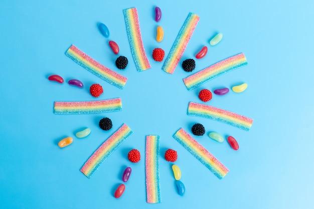 Una vista superior de mermeladas y caramelos de colores en azul, dulce azúcar dulce