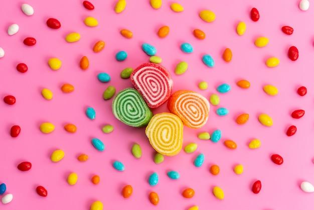 Una vista superior de mermeladas y caramelos coloridos composición forrada en rosa, color caramelo dulce