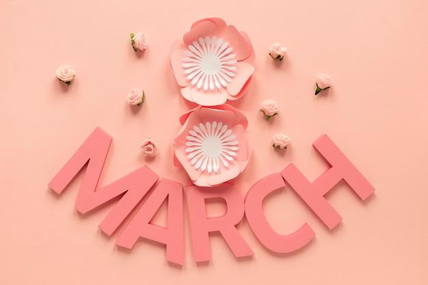 Vista superior del mes y flores de papel para el día de la mujer.