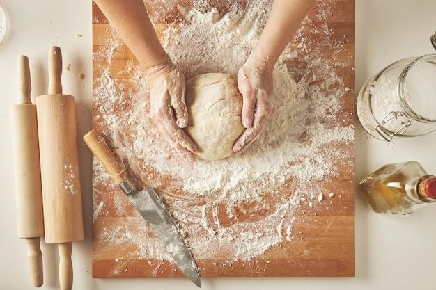 Vista superior de la mesa blanca con tablero de madera aislado con cuchillo, dos rodillos, botella de aceite de oliva, frasco transparente con harina manos de mujer sostienen masa preparada para pasta o bolas de masa hervida
