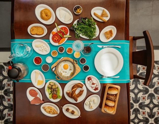 Vista superior mesa de desayuno con alimentos mixtos.
