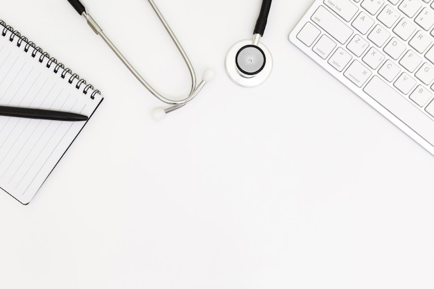 Vista superior de la mesa de escritorio del doctor, papel en blanco sobre blanco