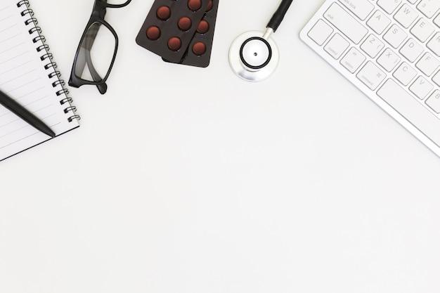 Vista superior de la mesa de escritorio del doctor con papel en blanco sobre blanco