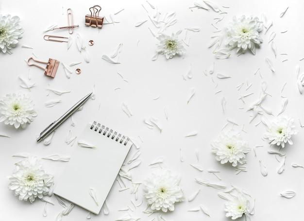 Vista superior de la mesa de escritorio de negocios con flores y simulacros de accesorios sobre fondo blanco.