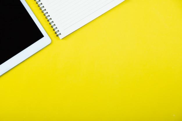 Vista superior de la mesa de escritorio de oficina amarilla con un montón de cosas en él.
