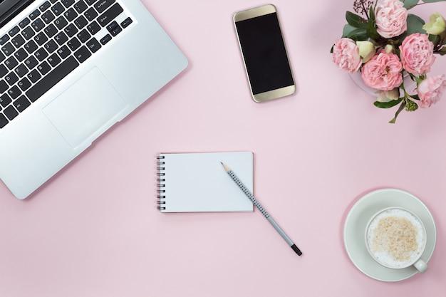 Vista superior de la mesa de escritorio de oficina rosa con ordenador portátil, teléfono inteligente, taza de café y flores. copia espacio, plano.