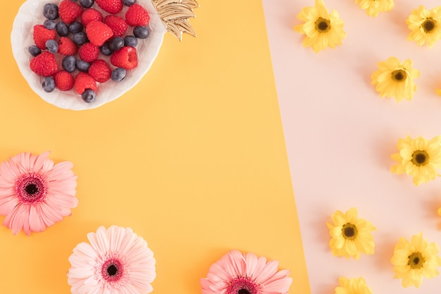 Vista superior de la mesa de escritorio de verano de oficina con flores y bayas en un plato de piña sobre fondo amarillo y rosa pastel. vacaciones de trabajo, concepto de verano. aplanada