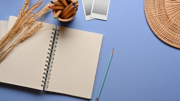 Vista superior de la mesa de estudio con cuaderno en blanco, lápices de colores, marcos de tarjetas fotográficas y decoraciones
