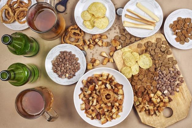 Vista superior de una mesa festiva llena de bocadillos y cerveza