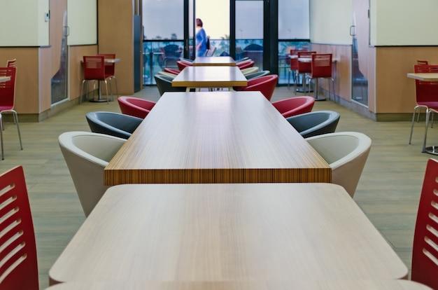 Vista superior de la mesa larga de madera de color amarillo-marrón con sillas azules y blancas. detalles del interior de la cafetería en el centro comercial. copia vacía espacio para texto.