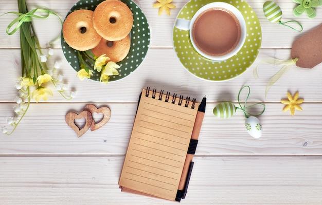 Vista superior de la mesa de madera blanca con taza de café, plato de galletas, huevos de pascua y flores de primavera